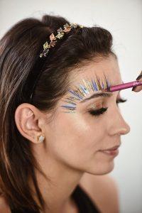 Aline Flores usando make fácil de fazer para o carnaval, com efeito de penas e muito glitter